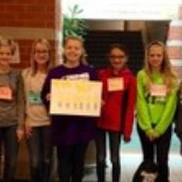6 girl scouts holding a sign with nametags